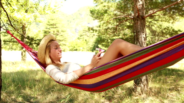 Cheerful girl on hammock in summer using digital tablet