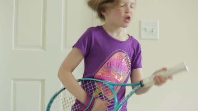 cheerful girl pretending to playing guitar with badminton at home - kind im grundschulalter stock-videos und b-roll-filmmaterial