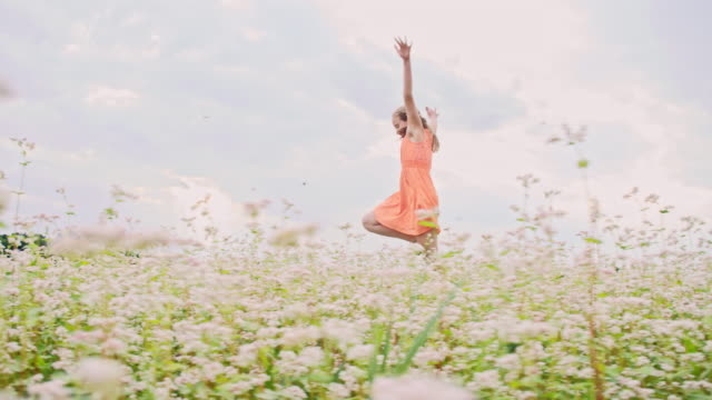 slo mo cheerful girl skipping and spinning in the field - dress stock videos and b-roll footage