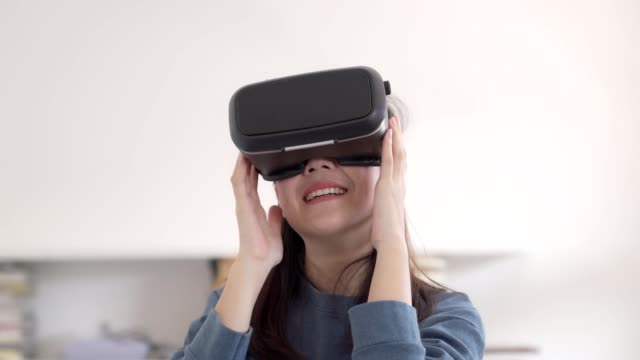cheerful girl uses a virtual reality glasses or vr in bed room with happy and exited feeling - gamepad stock videos & royalty-free footage