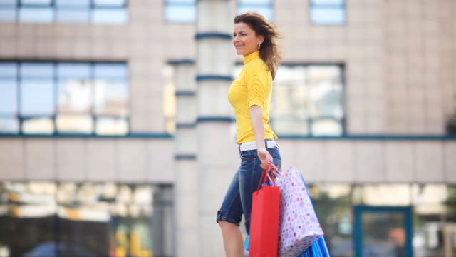 Cheerful girl walking  with shopping bags .