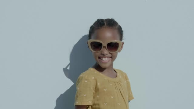 Cheerful girl wearing sunglasses against blue background