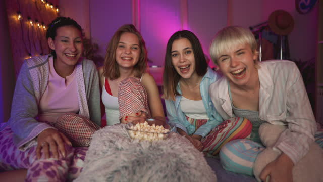 cheerful girlfriends at sleepover eating popcorns and watching a movie on a tv - slumber party stock videos & royalty-free footage