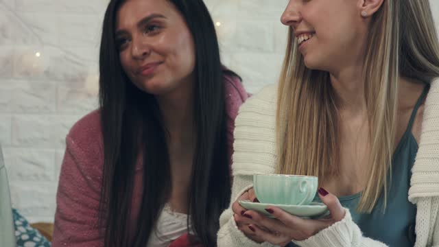 cheerful girlfriends enjoying tea in bed during a sleepover - slumber party stock videos & royalty-free footage
