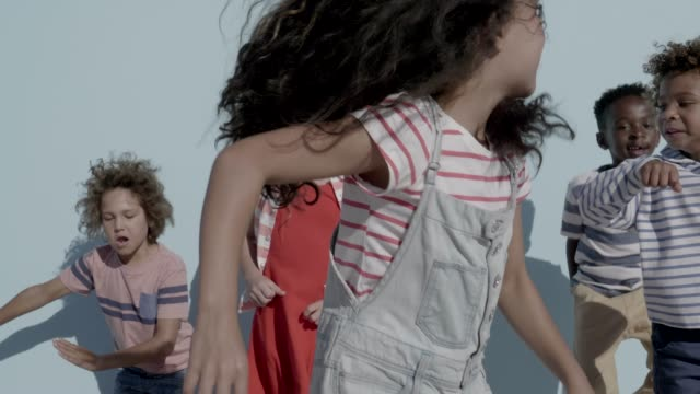 vidéos et rushes de cheerful girls and boys dancing against blue background - enfant