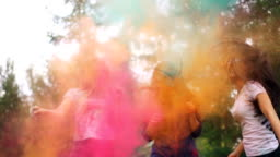 Cheerful girls are having fun dancing and laughing in clouds of powder paint at Holi festival wearing trendy clothing stained with paint. Youth and happiness concept.