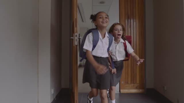 cheerful girls running in corridor of school - uniform stock videos & royalty-free footage