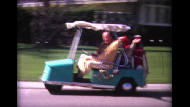 1965 cheerful group drives by in golf cart - golf cart stock videos and b-roll footage
