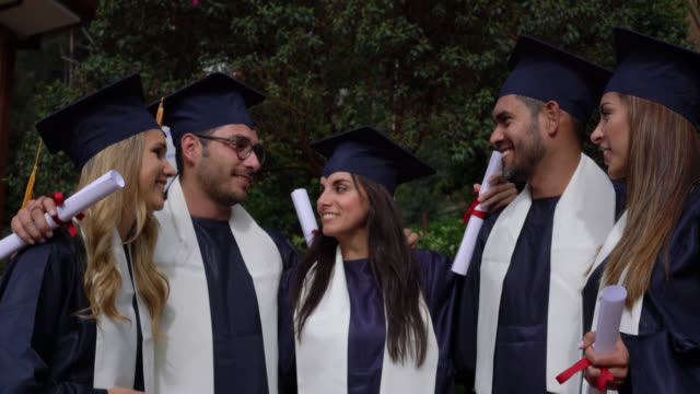 cheerful group of adult students celebrating they just graduated with high five and smiling - ceremony stock videos and b-roll footage