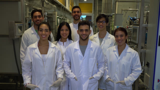 cheerful group of chemistry students at a laboratory facing camera smiling very happy - chemical stock videos & royalty-free footage