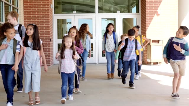 cheerful group of elementary and middle school students leaving school - first day of school stock videos & royalty-free footage