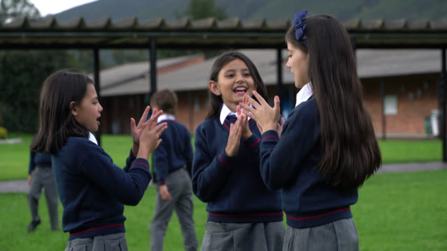 cheerful group of female friends playing a game during their break time at the school playground - school uniform stock videos & royalty-free footage