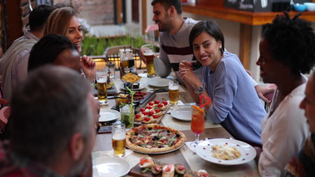 cheerful group of friends enjoying time together at outdoor gastro pub - happy hour stock videos & royalty-free footage