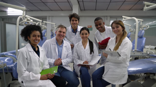cheerful group of students and dentistry teacher all smiling at camera very happy - lab coat stock videos & royalty-free footage