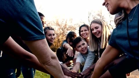 vídeos y material grabado en eventos de stock de grupo alegre de voluntarios ponen sus manos juntas en unidad después de un evento de limpieza en el vecindario - caridad y auxilio