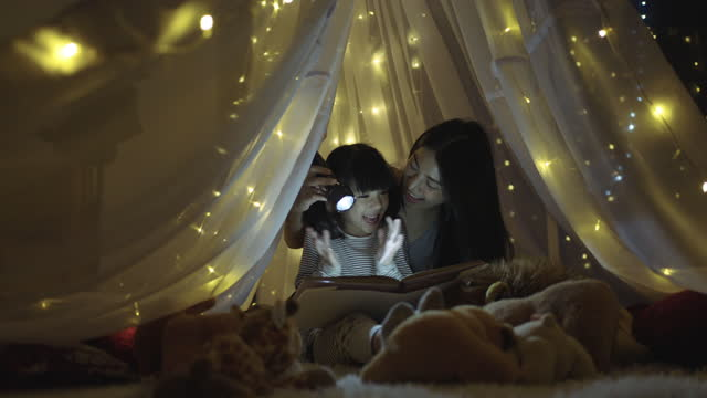 cheerful happy girl loving her mother reading story book at night - fairytale stock videos & royalty-free footage