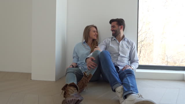 vidéos et rushes de jeune couple marié heureux gai appréciant le premier jour dans leur nouvelle maison - jeune couple