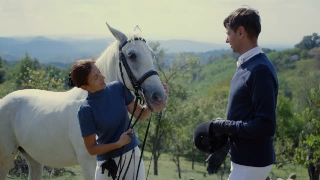 cheerful horseback riders by the white horse - recreational horseback riding stock videos & royalty-free footage