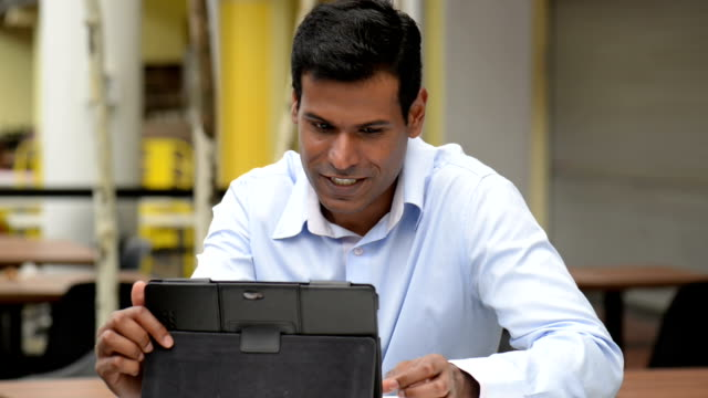 cheerful indian businessman using digital tablet at outdoor cafe - handsome people stock videos & royalty-free footage