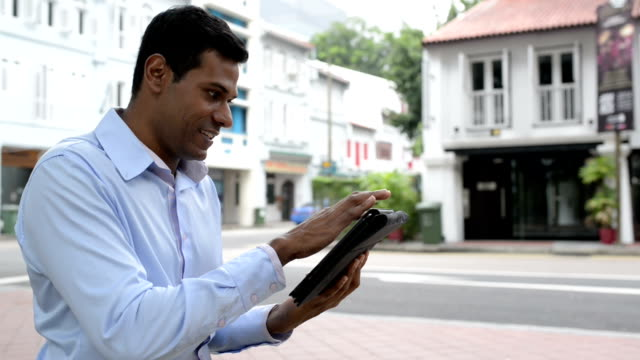 cheerful indian businessman using digital tablet at outdoor - male animal stock videos & royalty-free footage