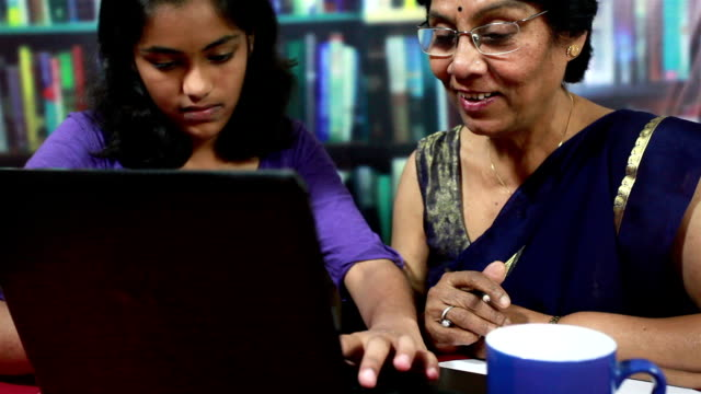 cheerful indian senior woman and teenager girl using laptop - asian stock videos & royalty-free footage