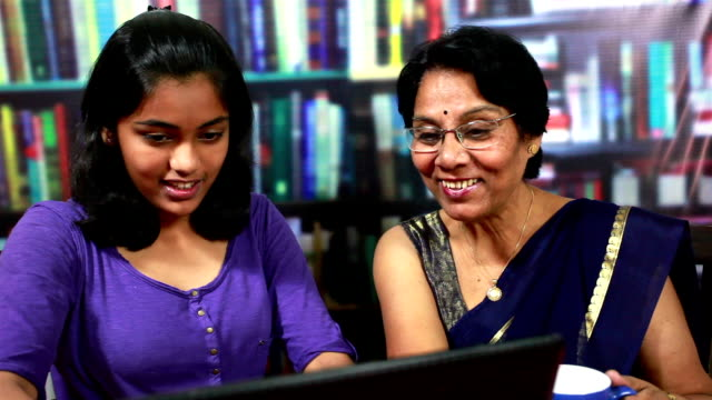 cheerful indian senior woman and teenager girl using laptop - showing stock videos & royalty-free footage