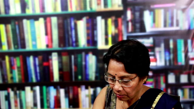 stockvideo's en b-roll-footage met cheerful indian senior woman using laptop in a library - internet surfen
