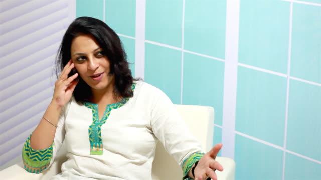 vídeos de stock e filmes b-roll de alegre mulher indiana a falar ao telefone - só uma mulher de idade mediana