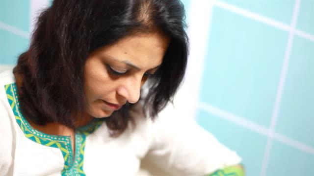 vídeos de stock e filmes b-roll de alegre mulher indiana usando o computador portátil em casa - só uma mulher de idade mediana