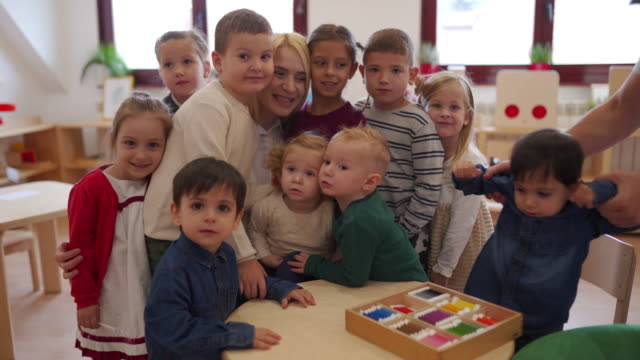 cheerful kids and their teacher in child care classroom - arms raised stock videos & royalty-free footage