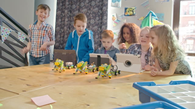 cheerful kids launching robot toys with tablets in classroom - mint themengebiet stock-videos und b-roll-filmmaterial
