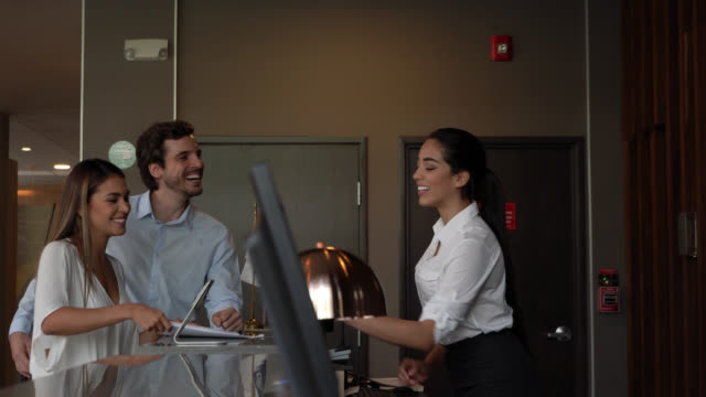 vídeos y material grabado en eventos de stock de alegre pareja de negocios de américa latina en firmar formularios con la ayuda de recepcionista de hotel - recepcionista