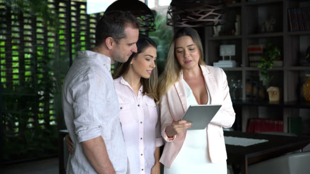 cheerful latin american couple looking at a property with a real estate agent while she shows some things on tablet and points away - insurance agent stock videos & royalty-free footage