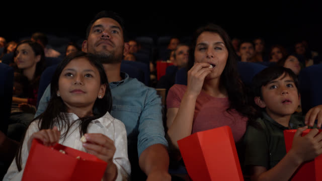 cheerful latin american family talking and enjoying popcorn at the cinema before the movie starts - cinema stock videos & royalty-free footage