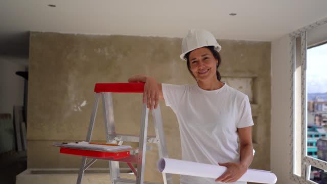 vidéos et rushes de travailleur de construction américain latin gai se penchant sur l'échelle et retenant un plan tout en souriant à l'appareil-photo - artisant