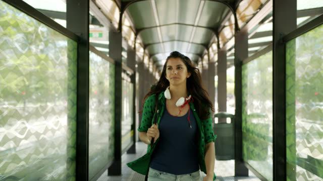 vídeos y material grabado en eventos de stock de alegre estudiante latinoamericano caminando en el refugio de autobuses sonriendo - latin american and hispanic ethnicity