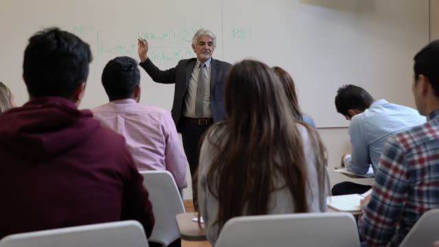 cheerful latin american teacher explaining to his class a formula on board and students raising their hands - post secondary education stock videos & royalty-free footage