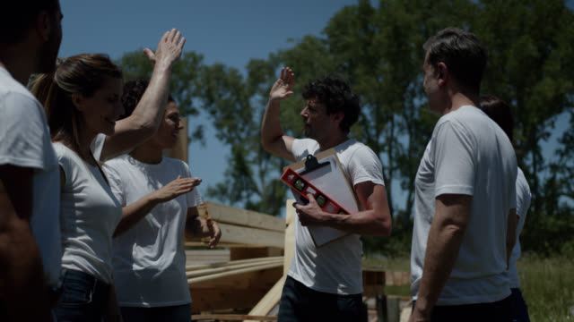 cheerful leader motivating his volunteer group at a construction site to build a charity home - giving stock videos & royalty-free footage