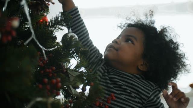 vídeos de stock, filmes e b-roll de menina afro pequena alegre em casa no tempo do natal - árvore de natal