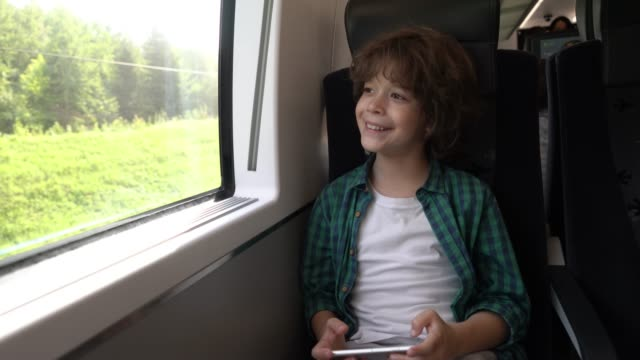 cheerful little boy playing a game on smartphone and looking at view while commuting on train - treno video stock e b–roll