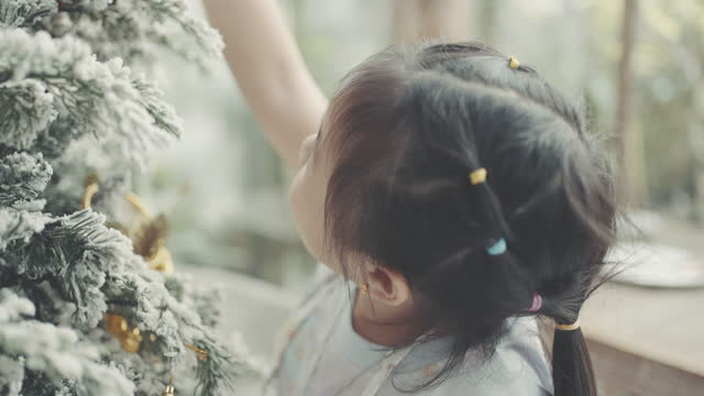 vídeos de stock e filmes b-roll de cheerful little girl decorating christmas tree - 6 7 years