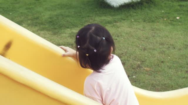 vídeos de stock, filmes e b-roll de menina alegre em slide no recreio - deslizar