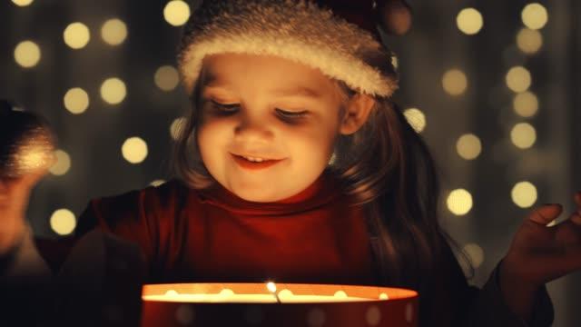 glad liten flicka leker med en jul prydnad hon hittade i en glödande presentförpackning - endast en flickbaby bildbanksvideor och videomaterial från bakom kulisserna
