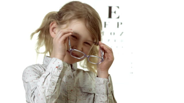 stockvideo's en b-roll-footage met hd: cheerful little girl putting on glasses - bril brillen en lenzen