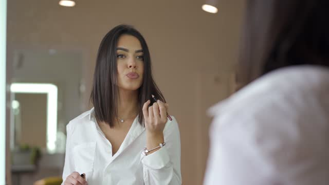 cheerful make up artist re-touching her lips with lipliner - lip liner stock videos & royalty-free footage
