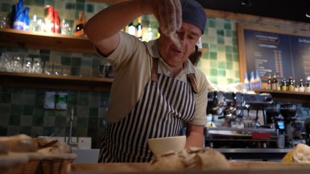 cheerful male baker sprinkling flour on bread very happy - sprinkling stock videos & royalty-free footage