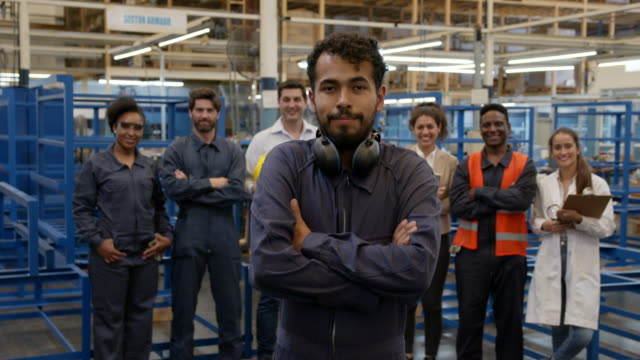 cheerful male blue collar worker wearing protective ear muffs on neck smiling at camera and group of employees standing behind - manufacturing machinery stock videos & royalty-free footage