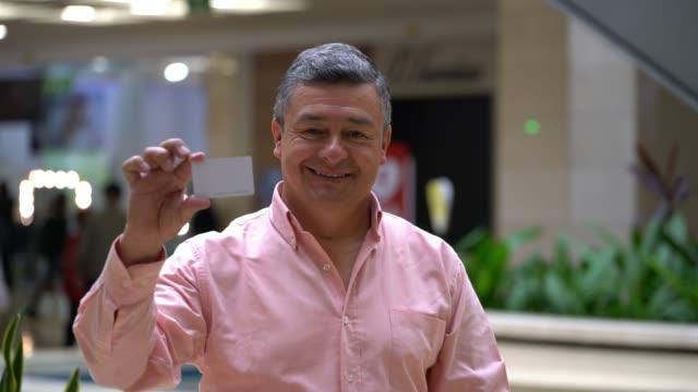 vidéos et rushes de client mâle gai au centre commercial montrant une carte pour éditer tout en faisant face au sourire de caméra - carte de fidélité