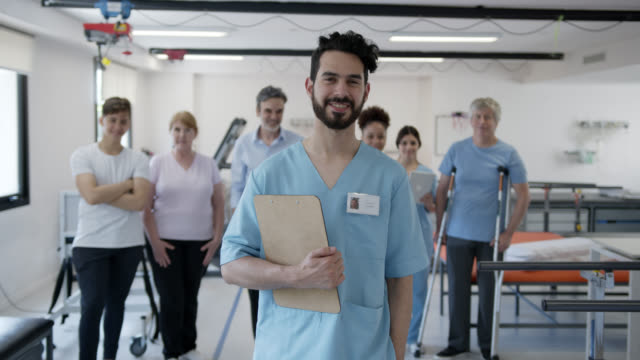 vídeos de stock e filmes b-roll de cheerful male physical therapist holding a clipboard smiling at camera and team of patients and professionals standing at background - fisioterapeuta