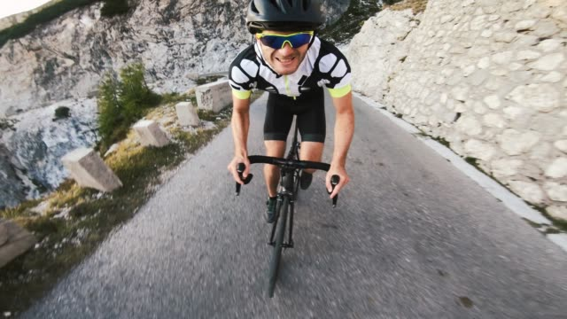 cheerful male road cyclist pedaling uphill in mountainside - racing bicycle stock videos & royalty-free footage